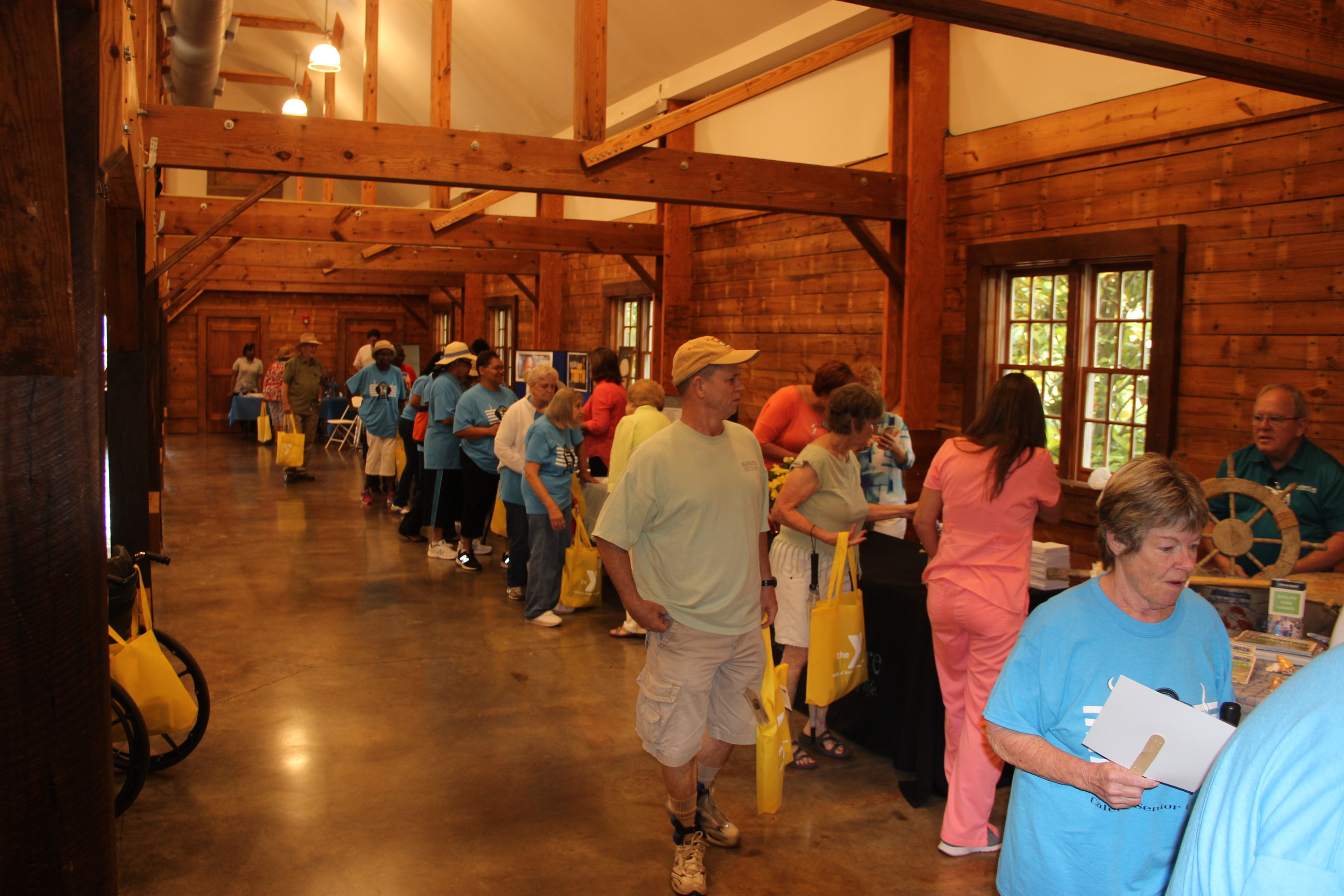 Image of guests cooling off in the vendor barn at the 2016 Senior Picnic