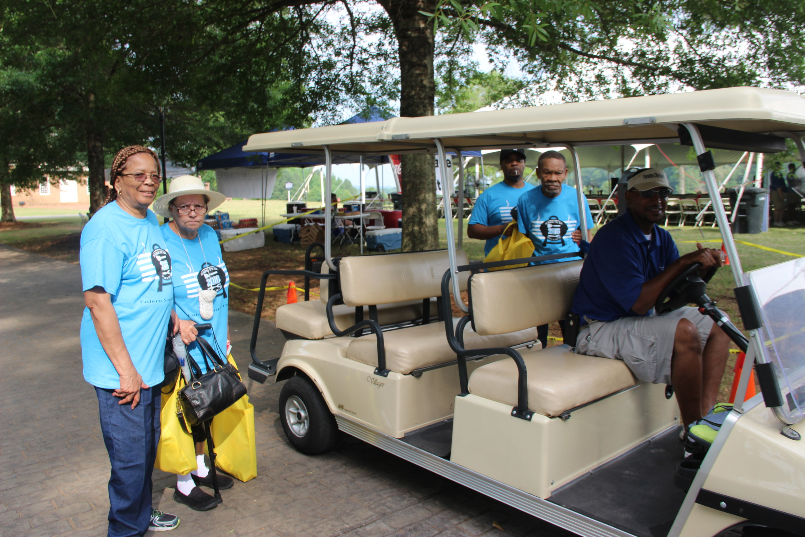 Image of people getting on the golf cart shuttle at the 2016 Senior Picnic