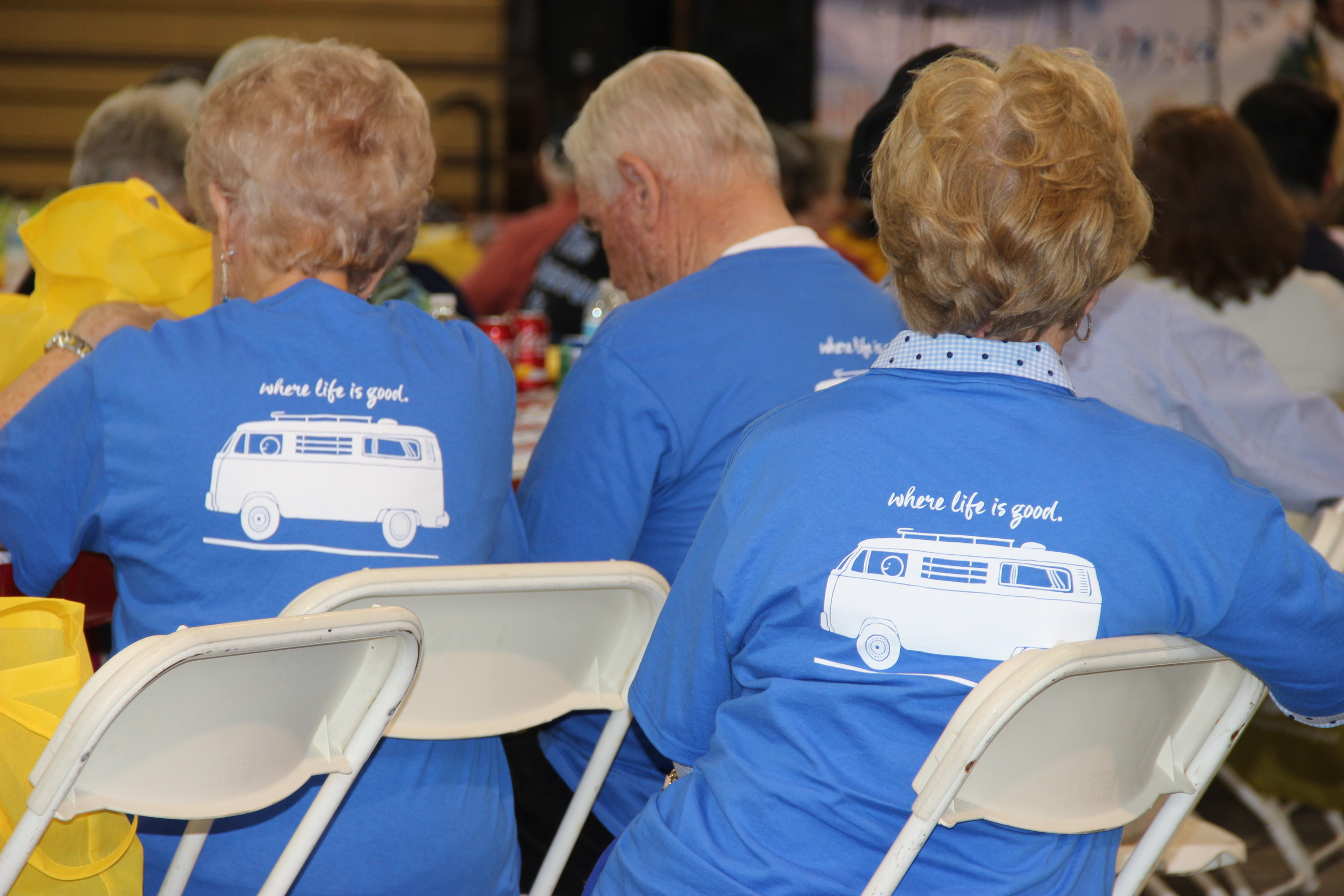 Image of three attendees wearing shirts that read 'When Life is Good' at the 2017 Senior Picnic